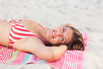 Woman smiling while sunbathing on a beach