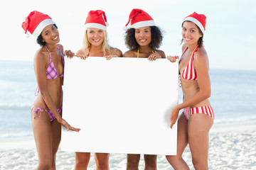 Four friends present a blank poster while wearing Santa hats