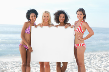 Four women smiling as they hold a large white poster