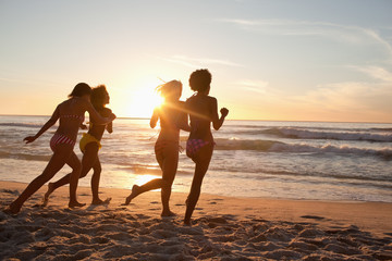 Four friends running across sand