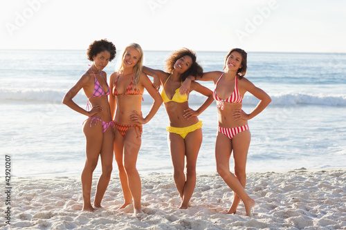 Four friends leaning on each other while smiling as they stand on the beach
