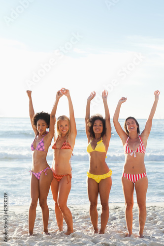 Four friends smiling while raising their arms on a beach