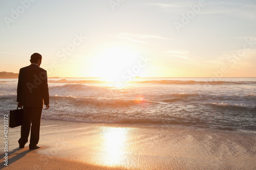 Businessman standing on a beach while looking at the horizon