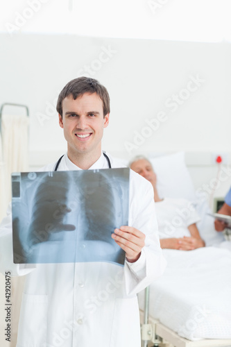 Doctor holding an x-ray scan with one hand