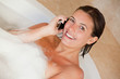 Smiling woman with her mobile phone in the tub