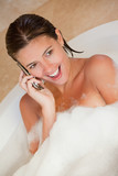 Surprised looking woman with her cellphone in the tub