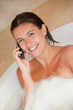 Smiling woman with her cellphone in the tub