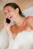 Laughing woman with her cellphone in the tub