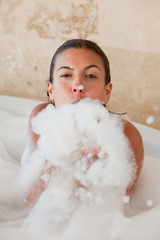 Woman in the tub blowing foam