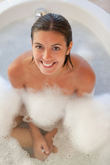 Smiling woman in the tub looking up