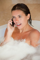 Surprised looking woman with her mobile phone in the tub