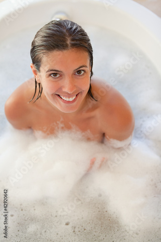 Smiling woman sitting in the tub and looking up