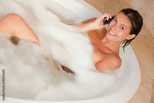 Smiling woman lying in the tub with her cellphone