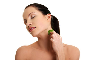 Young beautiful woman is applying aloe vera.
