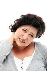 Woman grimacing in pain as she rubs her painful neck