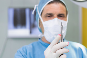Focus surgeon holding a scalpel in his hand