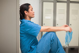 Thinking female surgeon sitting in a locker room