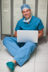 Surgeon sitting on the floor of a locker while holding a laptop