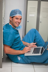 Surgeon sitting on the floor of a locker while using a laptop