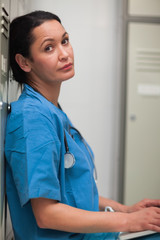 Female surgeon sitting in a locker room with a laptop