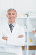 Smiling pharmacist with his arms folded standing in a pharmacy