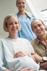 Smiling pregnant woman in a wheelchair with a nurse and a man