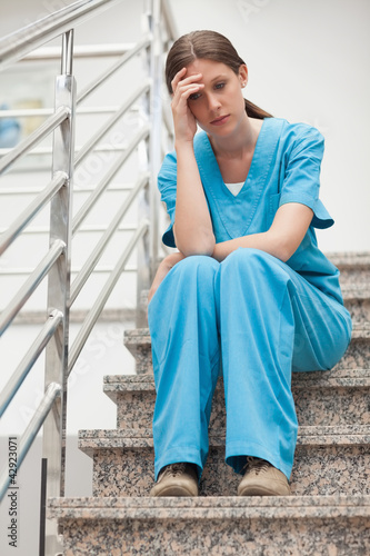 Thinking woman sitting on stairs
