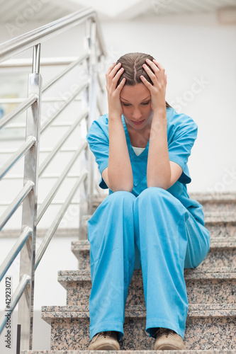 Nurse holding her head with her two hands in stairs