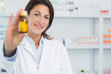Smiling female pharmacist showing pills and standing in a pharmacy