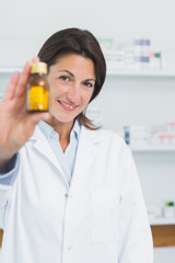 Smiling female pharmacist presenting pills and standing in a pharmacy