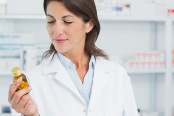 Female pharmacist looking at pills in a pharmacy