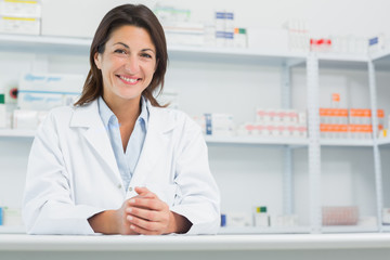 Smiling woman pharmacist behind a counter joining her hands