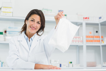 Smiling pharmacist holding a prescription behind the counter of a pharmacy