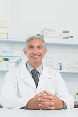 Smiling male pharmacist with his hands joined on a counter