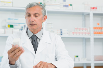 Serious pharmacist looking at a box full of pills
