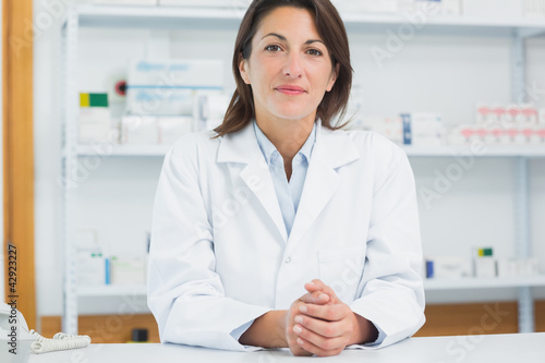 Woman pharmacist joining her hands on a counter