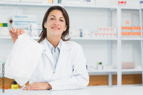 Smiling pharmacist woman holding a prescription