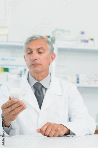 Pharmacist holding a box full of pills