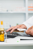 Pharmacist holding a prescription while using a computer on a desk