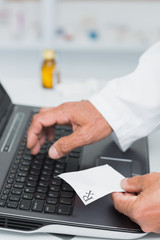 Pharmacist holding a prescription while typing on a computer