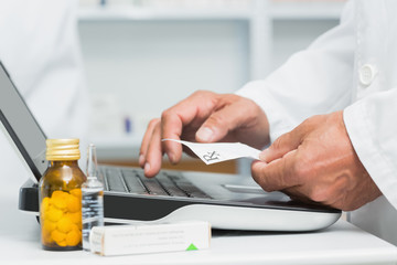 Pharmacist holding a prescription while typing on a computer on a desk