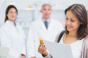 Female customer holding a paper and pills while standing in a pharmacy