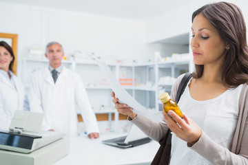 Female client holding a paper and pills while standing in a pharmacy