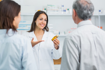 Pharmacist presenting a bottle of pills behind a counter