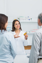 Pharmacist presenting a bottle of pills behind the counter of a pharmacy