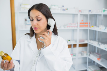 Pharmacist holding pills while phoning