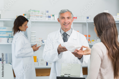 Pharmacist in a drugstore giving a bag of pills to a female client
