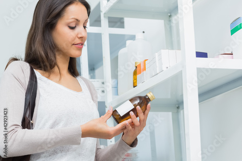 Client in a pharmacy holding a bottle of drug