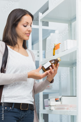 Customer in a pharmacy holding a bottle of drug