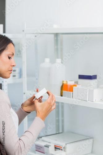 Woman looking at a box of pills